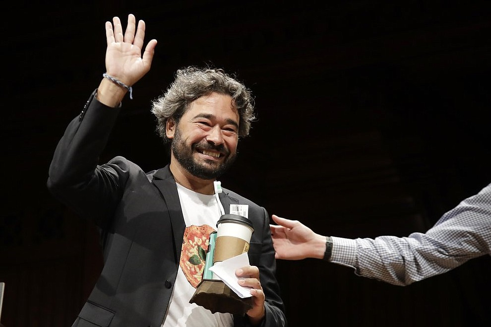Silvano Gallus, of Italy, waves as he receives the Ig Nobel award in medicine for collecting evidence that pizza might protect against illness and death, if the pizza is made and eaten in Italy, at the 29th annual Ig Nobel awards ceremony at Harvard University, Thursday, Sept. 12, 2019, in Cambridge, Mass. The spoof prizes for weird and sometimes head-scratching scientific achievement are bestowed by the Annals of Improbable Research magazine, and handed out by real Nobel laureates. (AP Photo/Elise Amendola)