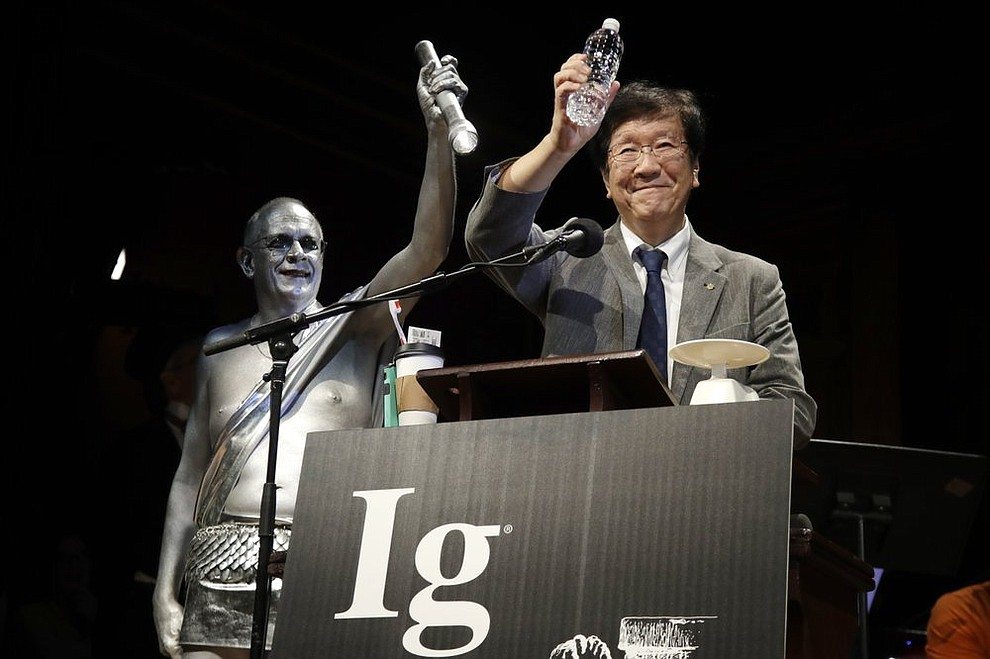 Shigeru Watanabe, of Japan, receives the Ig Nobel award in chemistry for estimating the total saliva volume produced per day by a typical five-year-old, at the 29th annual Ig Nobel awards ceremony at Harvard University, Thursday, Sept. 12, 2019, in Cambridge, Mass. The spoof prizes for weird and sometimes head-scratching scientific achievement are bestowed by the Annals of Improbable Research magazine, and handed out by real Nobel laureates. (AP Photo/Elise Amendola)
