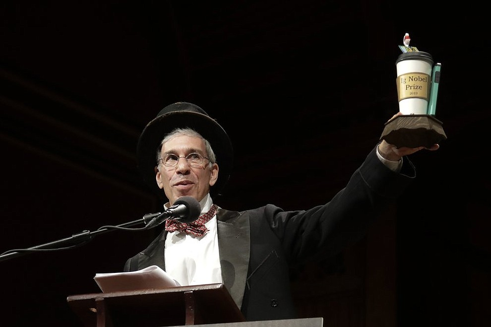 Marc Abrahams holds up the 2019 Ig Nobel award at the 29th annual Ig Nobel awards ceremony at Harvard University, Thursday, Sept. 12, 2019, in Cambridge, Mass. The spoof prizes for weird and sometimes head-scratching scientific achievement are bestowed by the Annals of Improbable Research magazine, and handed out by real Nobel laureates. (AP Photo/Elise Amendola)