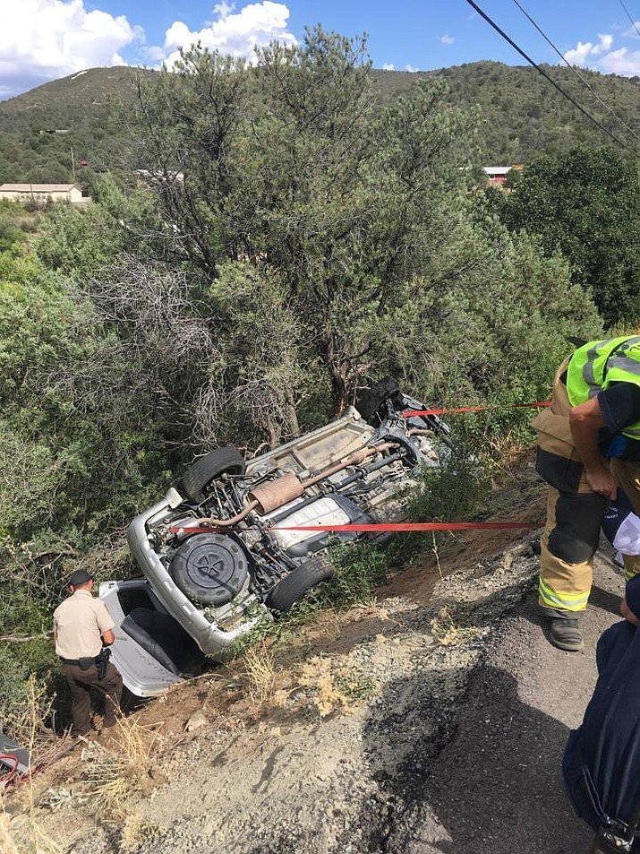 Firefighters secure a car that rolled off Robinson Road in Prescott and came to rest against a tree Saturday afternoon, Sept. 14, 2019. The driver sustained moderate injuries and was transported to the Yavapai Regional Medical Center in Prescott. (Dan Morgan, Prescott Fire Department/Courtesy)