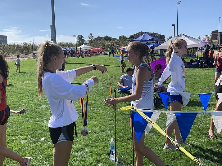 Prescott's Olivia Dunn (left) accepts her medal after finishing 12th in the Ray Wherley Invitational on Saturday, Sept. 14, 2019, at Emrby-Riddle Aeronautical University in Prescott. (Jake Whitaker/Courtesy)