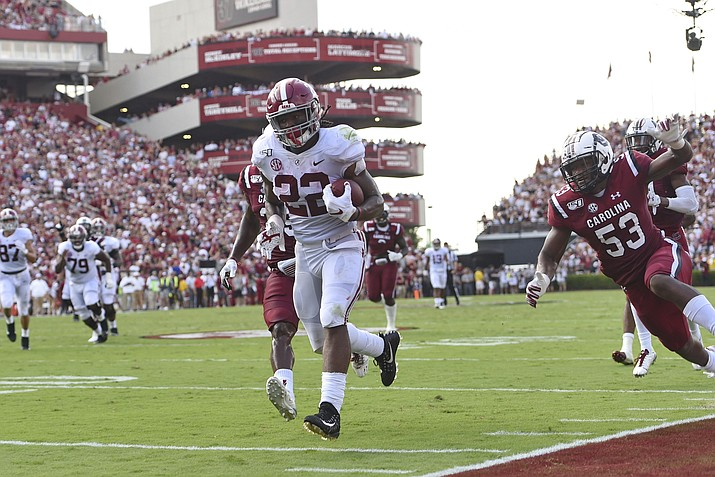 Alabama's Najee Harris, center, rushes past South Carolina's J.T. Ibe, left, and Ernest Jones for a touchdown during a game Saturday, Sept. 14, 2019, in Columbia, S.C. (Richard Shiro/AP)