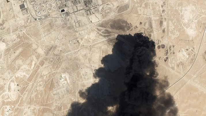 This Saturday, Sept. 14, 2019 satellite image from Planet Labs Inc. shows thick black smoke rising from Saudi Aramco's Abqaiq oil processing facility in Buqyaq, Saudi Arabia.  Yemen's Houthi rebels launched drone attacks on the world's largest oil processing facility in Saudi Arabia and a major oil field Saturday, sparking huge fires and halting about half of the supplies from the world's largest exporter of oil. (Planet Labs Inc. courtesy photo)