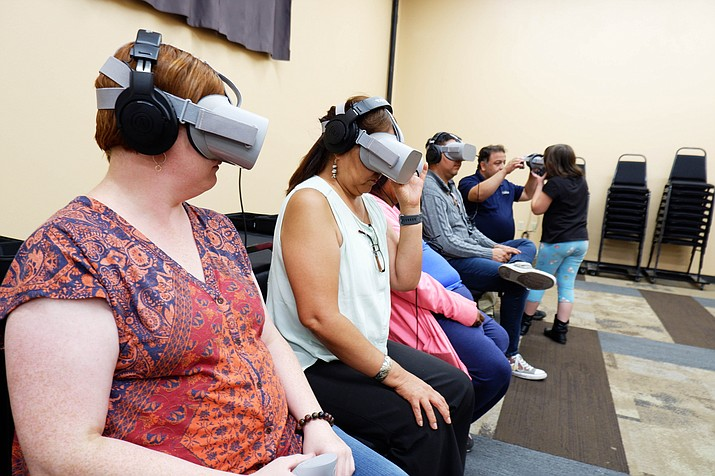 """Audience members try out virtual reality headsets to watch """"Ways of Knowing,"""" a film directed by artist Kayla Briet, at the El Morro Events Center in Gallup, New Mexico. Briet and other activists were using virtual reality technology like a 360 VR video rig cameras to focus on areas of the Navajo Nation affected by uranium contamination. (Adriel Luis/Ways of Knowing via AP)"""