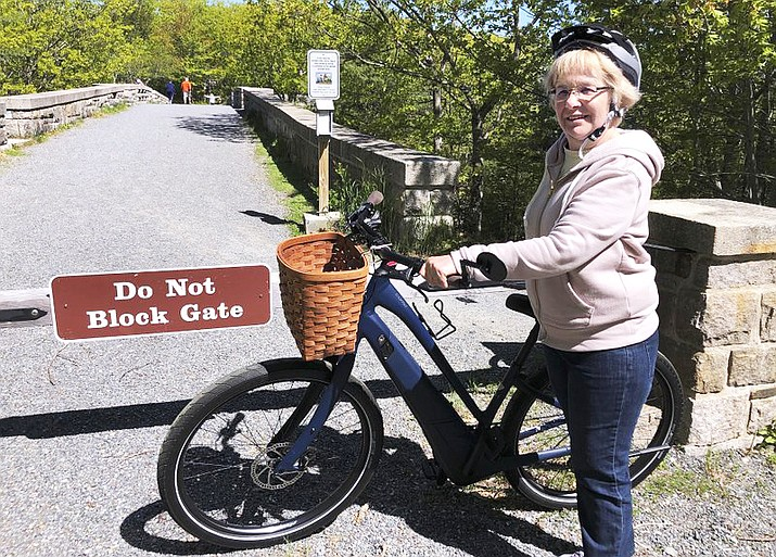 Janice Goodwin stands by her electric-assist bicycle at a gate near the start of the carriage path system where bikes such as hers are banned inside Acadia National Park. (AP Photo/David Sharp, files)