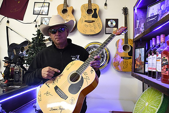 Mike Britt, songwriter and owner of Patriot Environmental, shows off one of the many guitars he took to Nashville to get them signed by the artists he met. (Photo by Vanessa Espinoza/Daily Miner)