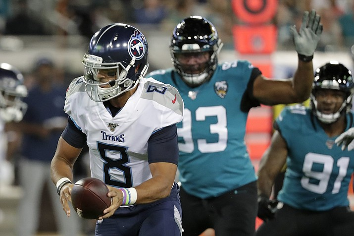 Tennessee Titans quarterback Marcus Mariota (8) looks to hand off the ball as he is pressured by Jacksonville Jaguars defensive end Calais Campbell, right, during the first half of an game, Thursday, Sept. 19, 2019, in Jacksonville, Fla. (John Raoux/AP)