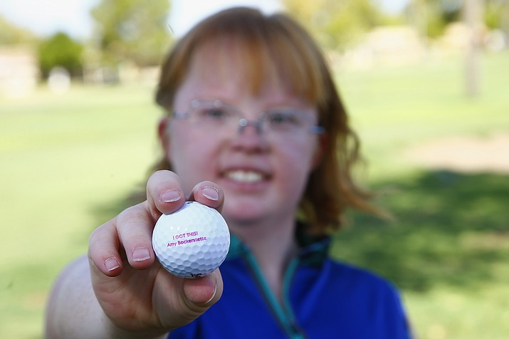 In this Aug. 28, 2019, photo, Amy Bockerstette, the golfer with Down syndrome who was an internet sensation by making par at the 16th hole at the Phoenix Open with soon-to-be 2019 U.S. Open champion Gary Woodland, smiles as she holds up a personalized logo golf ball after her golf lesson at Palmbrook Country Club in Sun City. (Ross D. Franklin/AP)