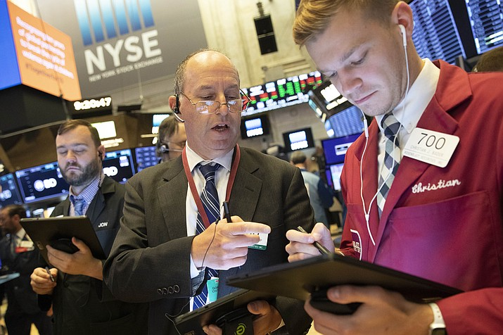 In this Sept. 16, 2019, file photo Gordon Charlop, center, and Christian Bader work at the New York Stock Exchange. The U.S. stock market opens at 9:30 a.m. EDT on Friday, Sept. 20. (AP Photo/Mark Lennihan, File)