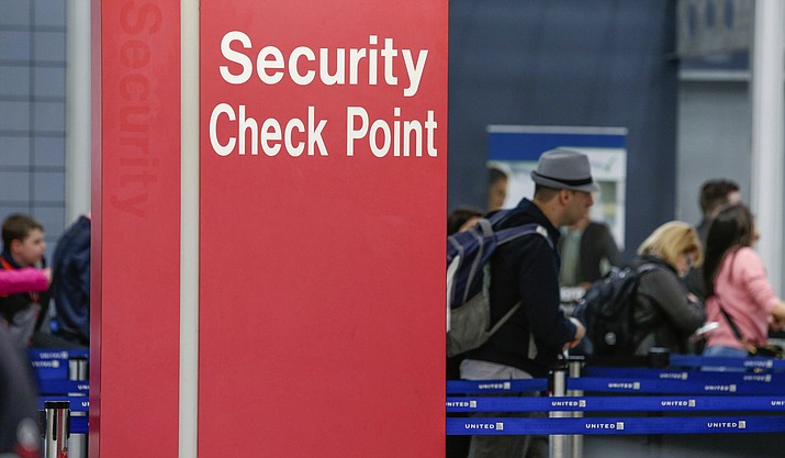 """In this March 22, 2016 file photo, passengers check into their flights near a security checkpoint sign at O'Hare International Airport in Chicago. The arrest of an airline mechanic suspected of being sympathetic with terrorists and charged with sabotaging a jetliner has renewed fear about the """"insider threat"""" to aviation security. Despite security upgrades since the hijacking terror attacks of 2001, breaches including a gun-running operation at the nation's biggest airport illustrate the possibility that a well-placed airline or airport employee could bring down a plane. (AP Photo/Teresa Crawford, File)"""