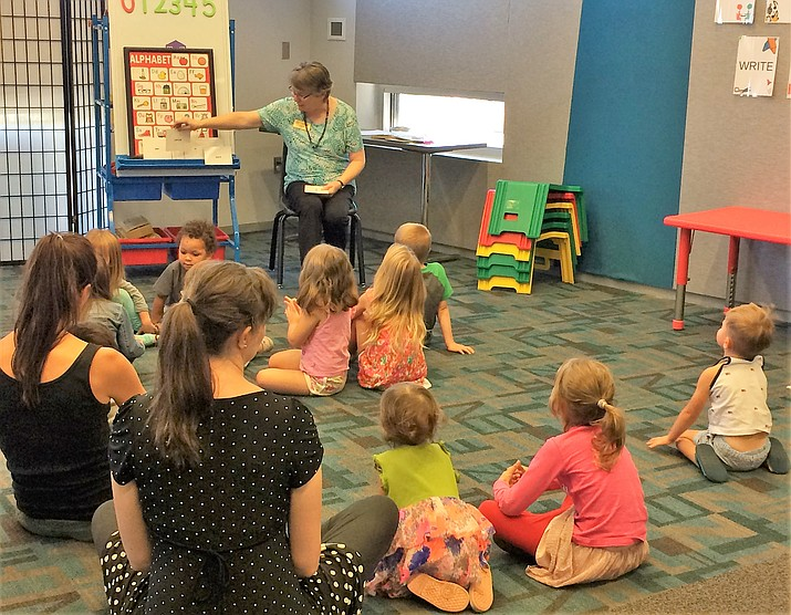 Children's Librarian Lynette Christensen reads three books and offers short activities at each Toddler Time session (11 a.m. Thursdays) at the Prescott Valley Public Library. About 17 youngsters ages 2-3 and their parents showed up for the Sept. 19 event. (Sue Tone/Courier)