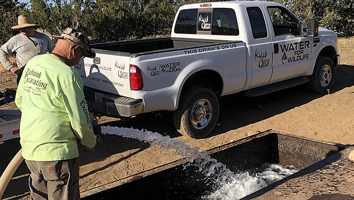 Arizona Elk Society volunteer Roger Hailey puts fresh, clean water back into a wildlife drinker that had been fouled by diesel fuel. (Arizona Elk Society courtesy photo)