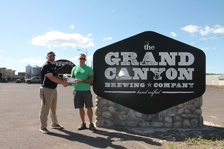 Williams High School Athletic Director Phillip Echeverria accepts a check from Grand Canyon Brewery CEO John Peasley Sept. 18. (Erin Ford/WGCN)