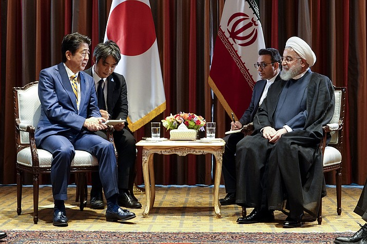 In this photo released by the official website of the office of the Iranian Presidency, President Hassan Rouhani, right, meets Japanese Prime Minister Shinzo Abe, left, on the sideline of the United Nations General Assembly at the United Nations, Tuesday, Sept. 24, 2019. (Iranian Presidency Office via AP)