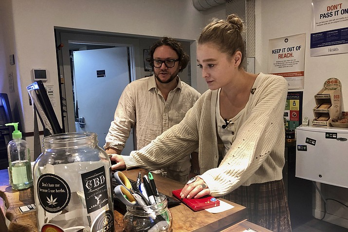"""In this photo taken Sept. 20, 2019, David Alport, owner of the Bridge City Collective marijuana dispensary in Portland, Ore., goes over sales numbers with the store's general manager Cameron Moore. The company has seen a 31% decrease in its sales of vaping products in the past two weeks. """"It's having an impact on how consumers are behaving,"""" said Alport. """"People are concerned, and we're concerned."""" (Gillian Flaccus/AP)"""
