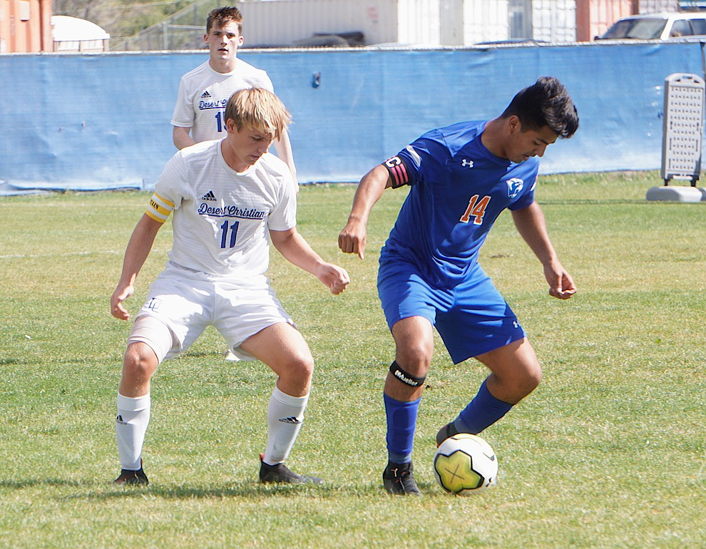 Chino Valley forward Angel Sanchez (14) shield the ball from a defender during the team's 8-2 win over Desert Christian on Saturday, Sept. 28, 2019, at Chino Valley High School. (Aaron Valdez/Courier)