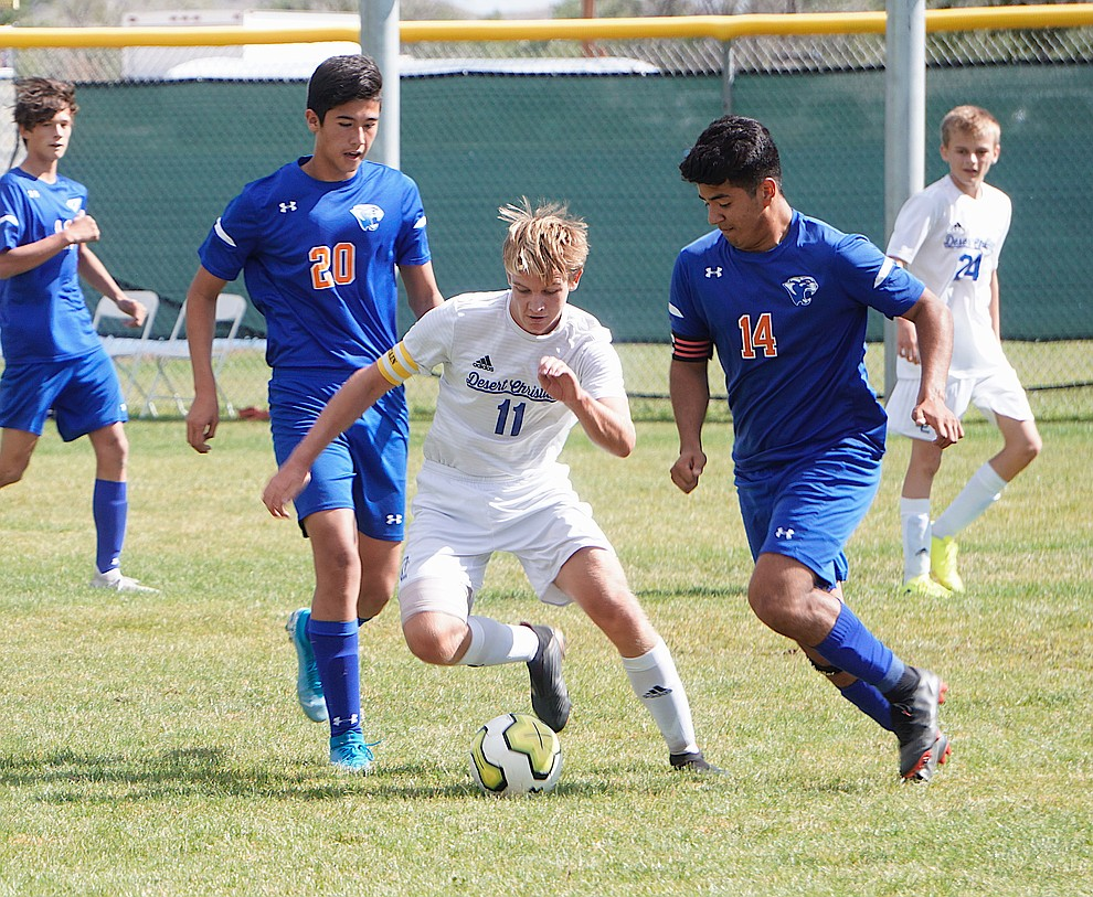 Desert Christian defender Jack Hutton (11) dribbles between Chino Valley's Angel Sanchez (14) and Ricardo Juarez-Flores during a game on Saturday, Sept. 28, 2019, at Chino Valley High School. (Aaron Valdez/Courier)