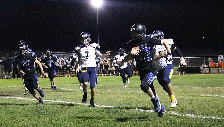Kingman Academy's Charlie Anderson runs the ball Friday night against Bourgade Catholic. The Tigers lost 58-13. (Photo by Travis Rains/Daily Miner)