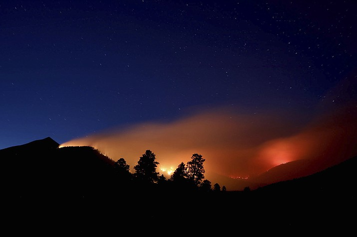 FILE- This July 21, 2019 photo shows pockets of wildfires within the Museum fire on the slopes of the San Francisco Peaks near Flagstaff, Ariz. Monsoon season carries high hopes for rain, thunder and lightning across the US Southwest, but it failed to deliver this year. Several communities in northern Arizona had the driest monsoon season on record, including Flagstaff. The season is characterized by a shift in wind patterns and moisture being pulled in from the tropical coast of Mexico. It runs from mid-June through September. (Jake Bacon/Arizona Daily Sun via AP)