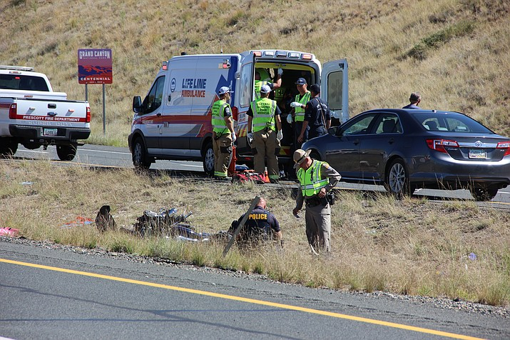 Police investigate a motorcycle crash on Highway 89A while paramedics treat the seriously-injured motorcyclist midday Monday, Sept. 30, 2019. (Max Efrein/Courier)
