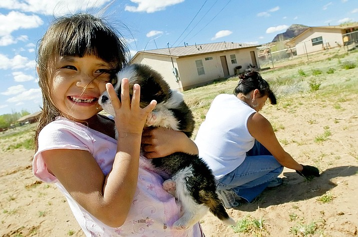 In this 2007 file photo, Cheyenne Yazzi hugs her puppy while her mother, Selina, pulls weeds in their backyard in Churchrock, N.M. Activists are using virtual reality technology to focus on areas of the Navajo Nation, like Churchrock, affected by uranium contamination. (Brian Leddy/Gallup Independent via AP, File)