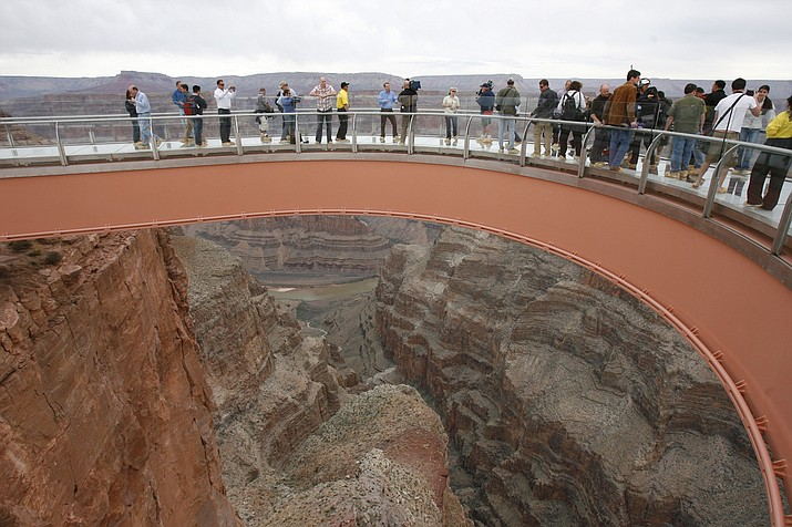 People walk on the Skywalk during the first walk event at the Grand Canyon on the Hualapai Indian Reservation at Grand Canyon West, Arizona. Authorities located the body of a man Sept. 30 who climbed over a safety barrier at the Grand Canyon Skywalk and apparently jumped to his death. (AP Photo/Ross D. Franklin, File)