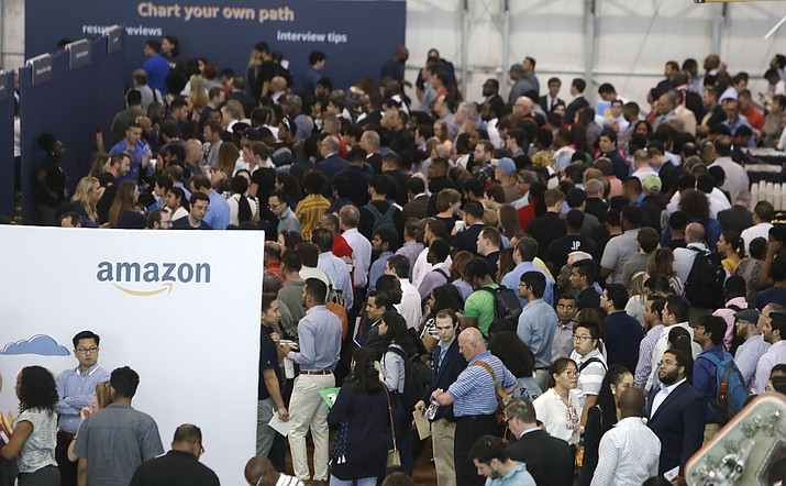 In this Sept. 17, 2019, photo job seekers line up to speak to recruiters during an Amazon job fair in Dallas. On Friday, Oct. 4, the U.S. government issues the September jobs report. (LM Otero/AP)