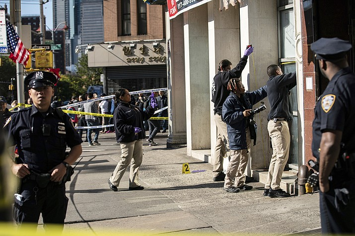 New York Police Department officers investigate the scene of an attack in Manhattan's Chinatown neighborhood, Saturday, Oct. 5, 2019 in New York. Four men who are believed to be homeless were attacked and killed early Saturday in a street rampage. NYPD Detective Annette Shelton said that a fifth man remained in critical condition after also being struck with a long metal object that authorities recovered. (AP Photo/Jeenah Moon)