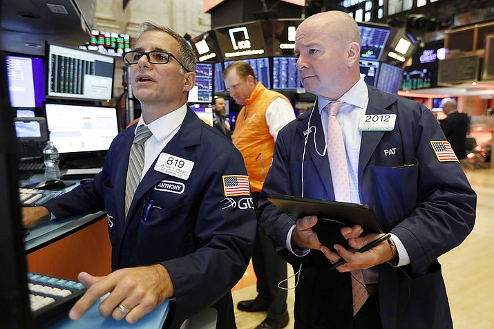 In this Sept. 13, 2019, photo specialist Anthony Rinaldi, left, and trader Patrick Casey work on the floor of the New York Stock Exchange. (Richard Drew/AP, File)