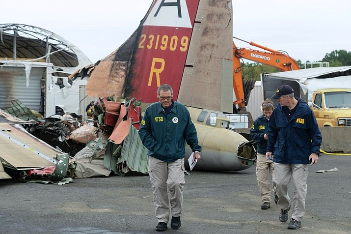 In this photo released via Twitter by the National Transportation Safety Board, NTSB investigator-in-charge Bob Gretz, left, walks Thursday, Oct. 3, 2019, with NTSB colleagues at the scene of a World War II-era bomber plane that crashed Wednesday at Bradley International Airport in Windsor Locks, Conn. (National Transportation Safety Board photo)