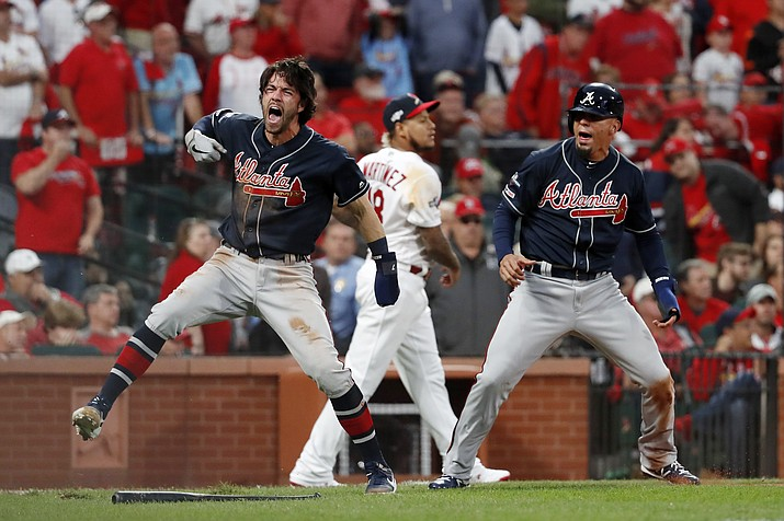 Atlanta Braves' Dansby Swanson, left, and Rafael Ortega, right, celebrate after scoring as St. Louis Cardinals relief pitcher Carlos Martinez (18) walks in the background during the ninth inning in Game 3 of a baseball National League Division Series on Sunday, Oct. 6, 2019, in St. Louis. (Jeff Roberson/AP)