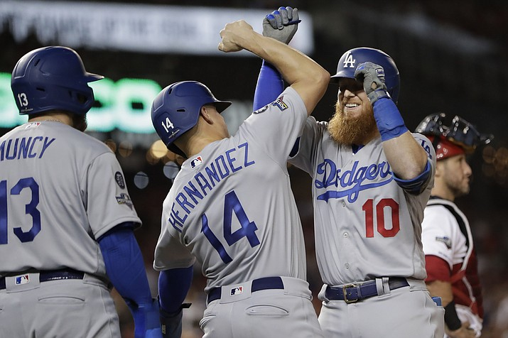 Los Angeles Dodgers third baseman Justin Turner (10) celebrates his three-run home run off Washington Nationals relief pitcher Wander Suero with teammates Enrique Hernandez (14) and Max Muncy (13) during the sixth inning in Game 3 of a baseball National League Division Series on Sunday, Oct. 6, 2019, in Washington. (Julio Cortez/AP)