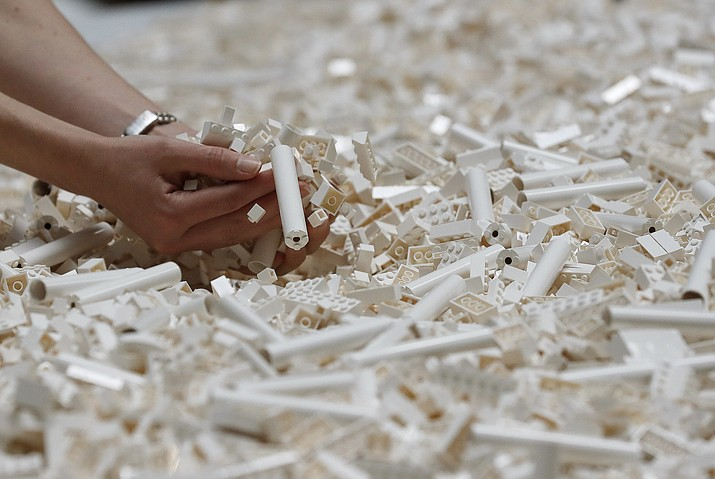 In this Friday July 26, 2019, file photo, a visitor looks through Lego pieces provided for a project at the Tate Modern, in London. Lego is testing a way for customers to ship their unwanted bricks back and get them into the hands of other kids. (AP Photo/Frank Augstein, File)