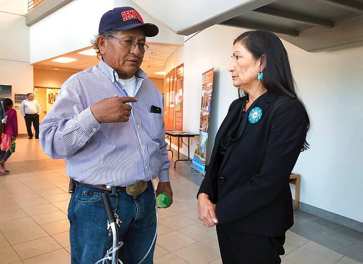 Leslie Begay, left, speaks with U.S. Rep. Deb Haaland, D-New Mexico, in a hallway outside a congressional field hearing in Albuquerque, N.M., highlighting the atomic age's impact on Native American communities on Monday, Oct. 7, 2019. Begay, a former uranium miner on the Navajo Nation with lung problems, says there are lingering injustices and health problems on his reservation decades after mines closed. An Indian Health Service official cited federal research at the hearing that she says showed some Navajo women, males and babies who were part of the study had high levels of uranium in their systems. (AP Photo/Mary Hudetz)