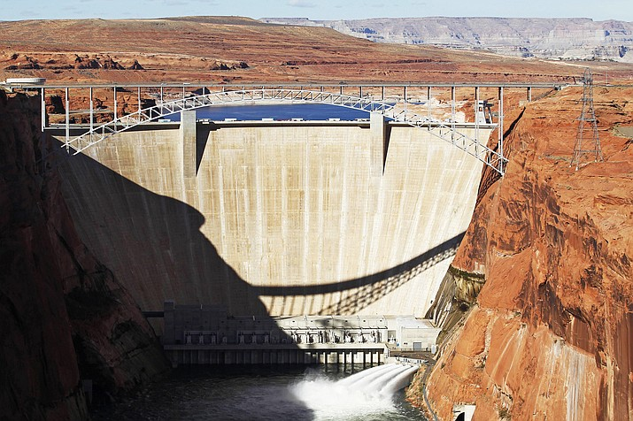 Water is released into the Colorado River at the Glen Canyon Dam in Page, Arizona in 2012. On Oct. 1, environmental groups filed a lawsuit against the federal government, saying that the U.S. Bureau of Reclamation ignored climate science when approving a 20-year operating plan for the dam. (Rob Schumacher/The Arizona Republic via AP, File)