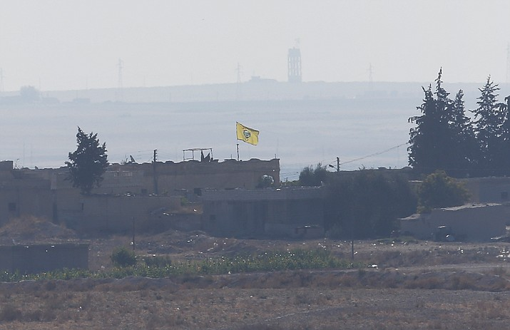 In this photo taken from the Turkish side of the border between Turkey and Syria, in Akcakale, Sanliurfa province, southeastern Turkey, a flag of Kurdish People's Protection Units, or YPG, flies on a building in the Syrian town of Tel Abyad, Tuesday, Oct. 8, 2019. Turkey's vice president says his country won't bow to threats in an apparent response to U.S. President Donald Trump's warning to Ankara about the scope of its planned military incursion into Syria aiming to create a zone that would allow Turkey to resettle Syrian refugees there. (Lefteris Pitarakis/AP)
