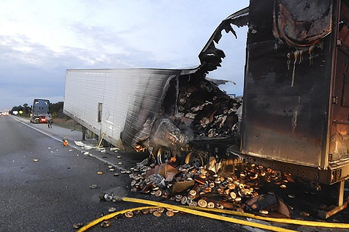 This Sunday, Oct. 6, 2019 photo provided by the Indiana State Police shows a load of frozen bagels that ended up toasted and strewn along a northwestern Indiana highway after a semi-trailer's rear axle caught fire near Rensselaer, Ind. State police say an off-duty trooper noticed smoke pouring from the rear of a box trailer being hauled Sunday along northbound Interstate 65. The southbound trooper turned around, but by the time he stopped the truck south of I-65's Rensselaer exit, its trailer's brakes were burning as the flames spread into its 38,000-pound load of frozen bagels. (Trooper Mason Wiley/Indiana State Police via AP)