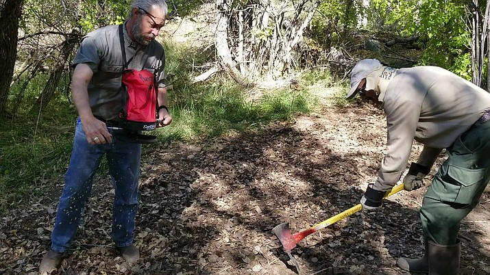 Prescott Creeks Executive Director Michael Byrd (left) spreads native grass seed in an area of Watson Woods that was previously covered in periwinkle, while Prescott Creeks volunteer John Mangimeli loosens the soil with a pickaxe on Thursday, Oct. 3, 2019. (Max Efrein/Courier)