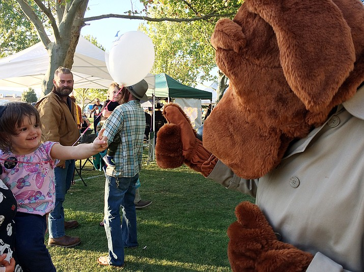 """Amelia Walter meets """"McGruff the Crime Dog"""" at the National Night Out event in Chino Valley on Tuesday, Oct. 1, 2019. The town's sixth annual National Night Out was held at Memory Park, designed to heighten crime and drug prevention awareness, generate support for and participation in local anti-crime efforts and to strengthen neighborhood spirit and police community partnerships. For more information, visit the Chino Valley Police Department's Facebook page. (Jason Wheeler/Review)"""