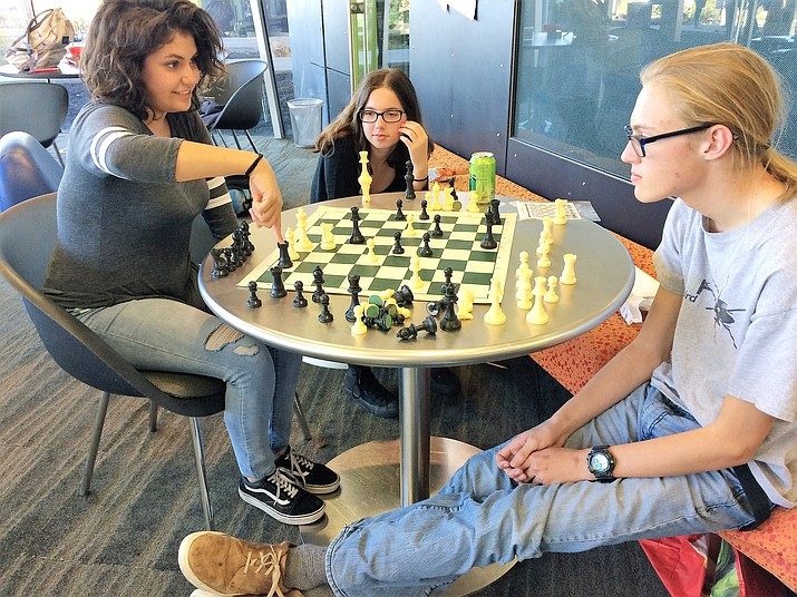 Sofia Alvarez, left, a junior at AAEC (Arizona Agribusiness & Equine Center), contemplates whether she's making a good move in her first game of chess ever on Oct. 3, 2019, in the Prescott Valley Public Library. Andrew Watkins, AAEC sophomore, right, is her instructor, and Sarah White, AAEC junior, the cheering squad. Chess is a popular activity for teens at the library. (Sue Tone/Tribune)