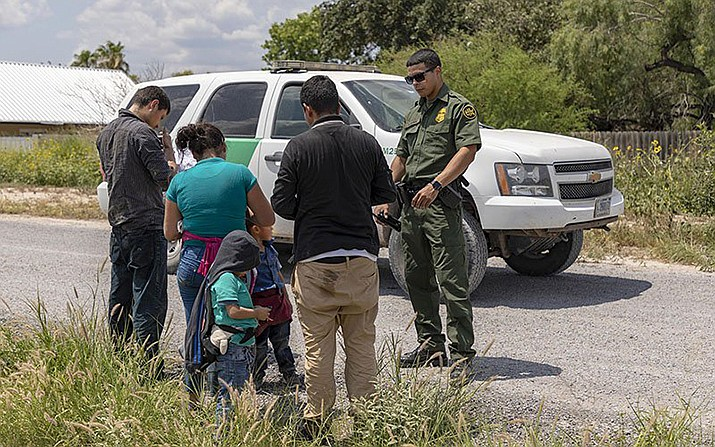 An immigrant family turns itself in to a Border Patrol agent after illegally crossing the Rio Grande in June. Border officials report that apprehensions are falling as an immigration crackdown continues. (Photo by Mani Albrecht/Customs and Border Protection)