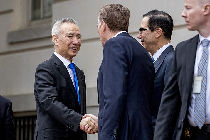 In this May 10, 2019, photo, China's Vice Premier Liu He, left is greeted by U.S. Treasury Secretary Steve Mnuchin, second from right, and U.S. Trade Representative Robert Lighthizer, third right, as he arrives at the Office of the United States Trade Representative in Washington. China's Ministry of Commerce said Tuesday that Liu is going to Washington on Thursday for talks aimed at ending the tariff war. (Andrew Harnik/AP, File)