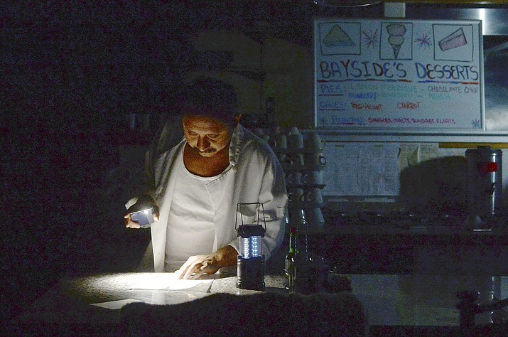 Carlos Lama of Bayside Cafe, which was among businesses to lose power due to PG&E's public safety power shutoff, uses an LED lamp and light from his phone at the counter of the restaurant in Sausalito, Calif., Wednesday, Oct. 9, 2019. Pacific Gas & Electric has cut power to more than half a million customers in Northern California hoping to prevent wildfires during dry, windy weather throughout the region. (Alan Dep/Marin Independent Journal via AP)