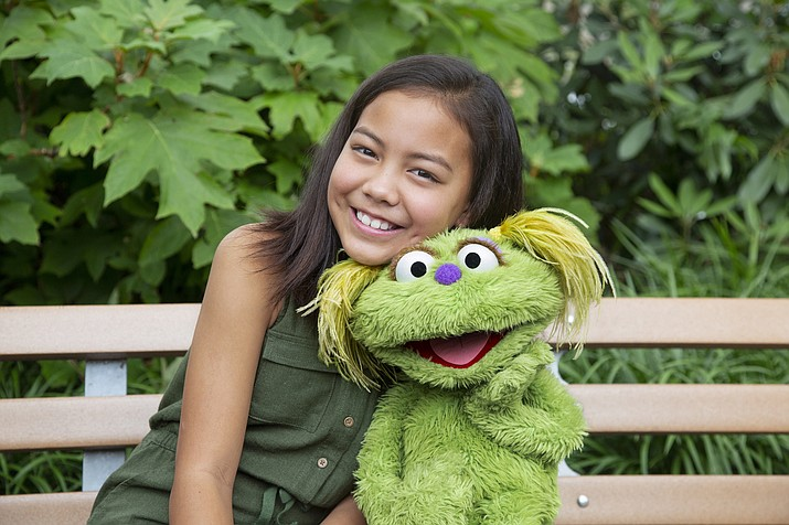 """This undated image released by Sesame Workshop shows 10-year-old Salia Woodbury, whose parents are in recovery, with """"Sesame Street"""" character Karli. Sesame Workshop is addressing the issue of addiction. Data shows 5.7 million children under 11 live in households with a parent with substance use disorder. Karli had already been introduced as a puppet in foster care earlier this year but viewers now will understand why her mother had to go away for a while. (Flynn Larsen/Sesame Workshop via AP)"""