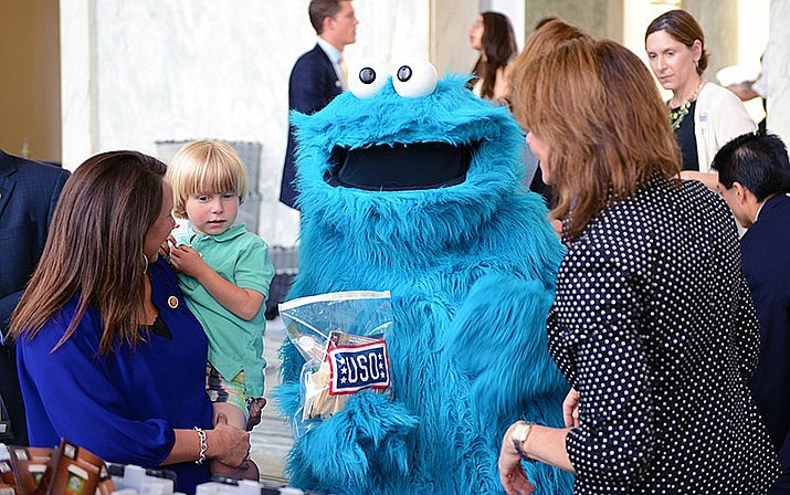 Martha Roby holds her 4-year-old son, George, as they greet Sesame Street's Cookie Monster during a biannual USO care package service project event on Capitol Hill in Washington, D.C., May 22, 2013 (Photo by DOD photo by Army Sgt. 1st Class Tyrone C. Marshall Jr., cc-by-sa-2.0, http://bit.ly/2Vwg0fu)