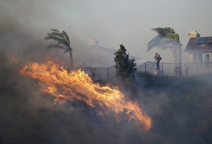 A firefighter sprays water in front of an advancing wildfire Friday, Oct. 11, 2019, in Porter Ranch, Calif. (Marcio Jose Sanchez/AP)