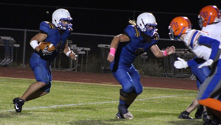 Kingman High's Austin Dias runs the ball as Powers Corbin blocks for him during a 20-16 win Friday night over Chino Valley. Dias finished with 122 rushing yards and two touchdowns. (Photo by Beau Bearden/Daily Miner)
