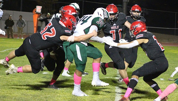 A pack of Volunteers, including Luigi Garibaldi (52) and Zach Allen (71), try to bring down Flagstaff's Luis Jaramillo. (Photo by Beau Bearden/Daily Miner)