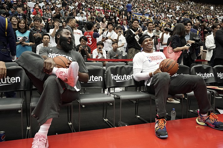 Houston Rockets' James Harden, left, and Russell Westbrook share a light moment during warmups for the team's NBA preseason basketball game against the Toronto Raptors Thursday, Oct. 10, 2019, in Saitama, near Tokyo. (Jae C. Hong/AP, file)
