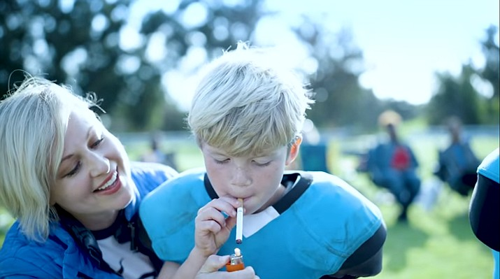 "A ""Tackle Can Wait"" campaign public service announcement shows a mom lighting a cigarette for her son, who is a youth football player. The PSA aims to show how youth ages 5 to 14 are 10 times more likely to get the brain disease CTE by playing tackle football. (Screenshot)"